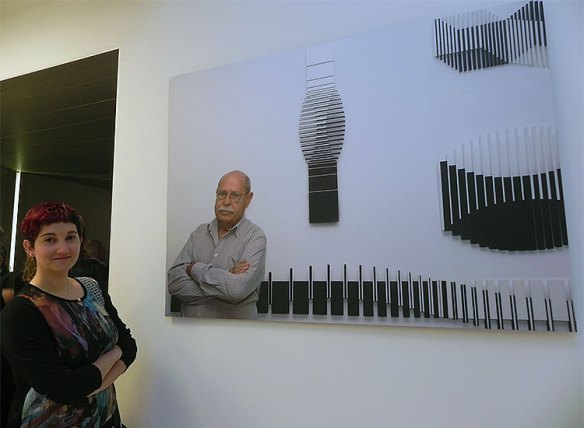 La fotógrafa alcarreña Paula M. Langa, junto al retrato que hizo a Sobrino y que luce en su museo. // Foto: E.C. (Cultura EnGuada).
